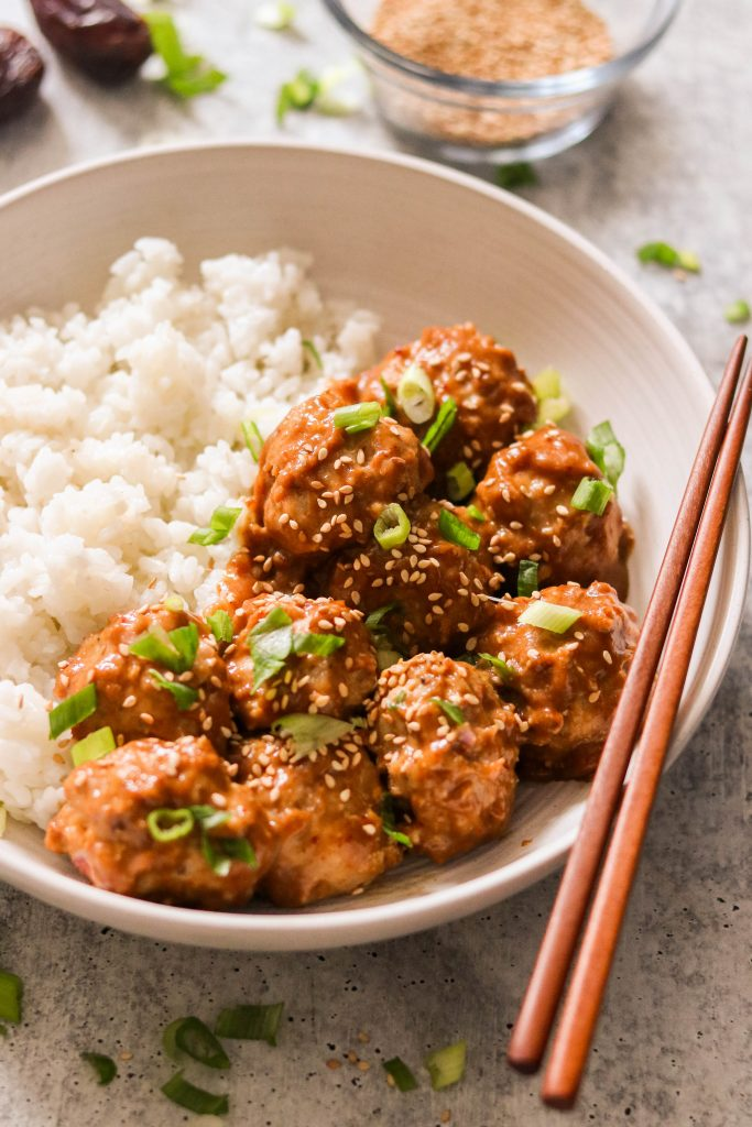 Sticky asian chicken meatballs in a bowl with rice