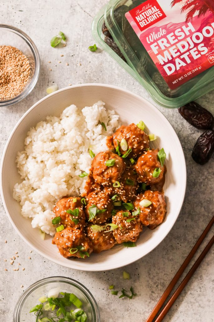 baked asian chicken meatballs covered in sauce served over rice