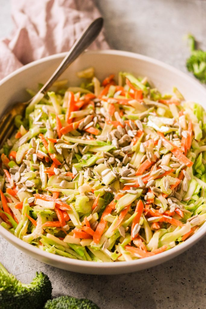 broccoli and carrot slaw served with a fork in a dish