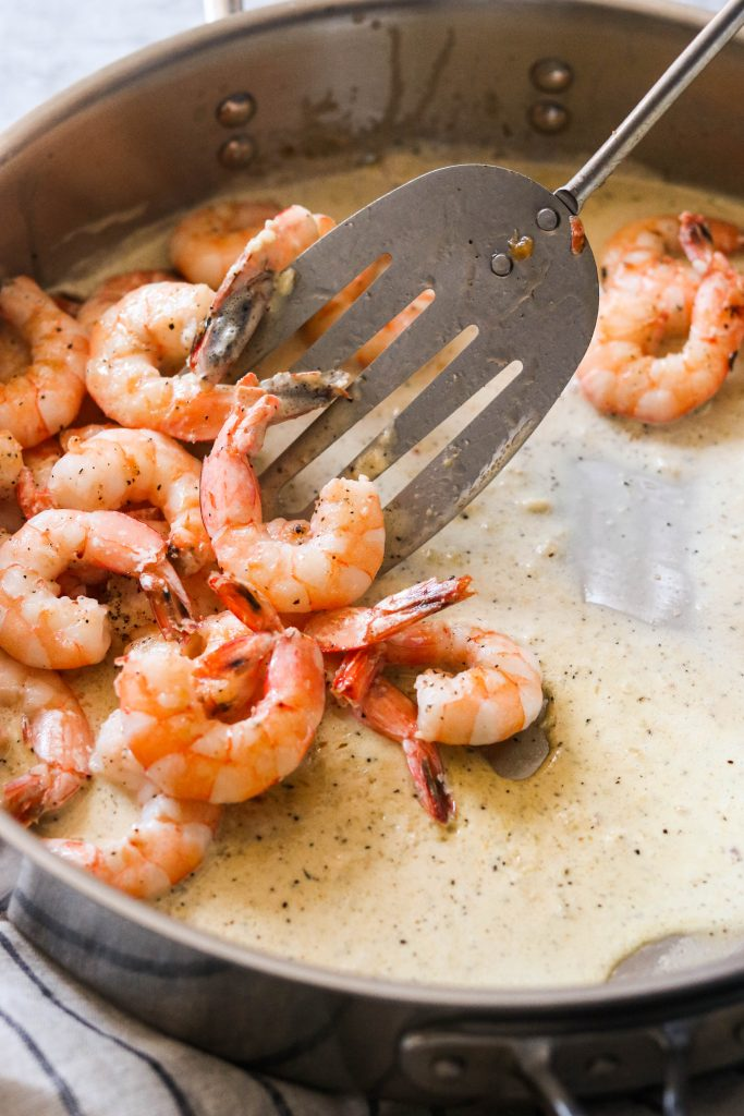 Adding cooked shrimp to creamy garlic sauce in a pan