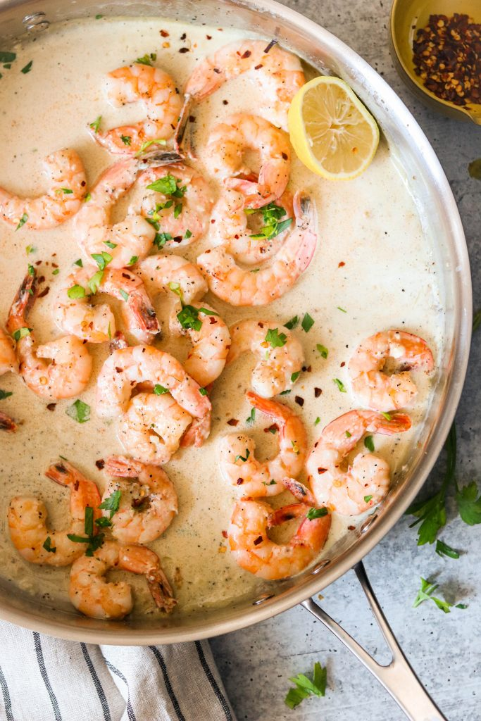 Shrimp in a skillet in creamy sauce, sprinkled with parsley and red pepper flakes