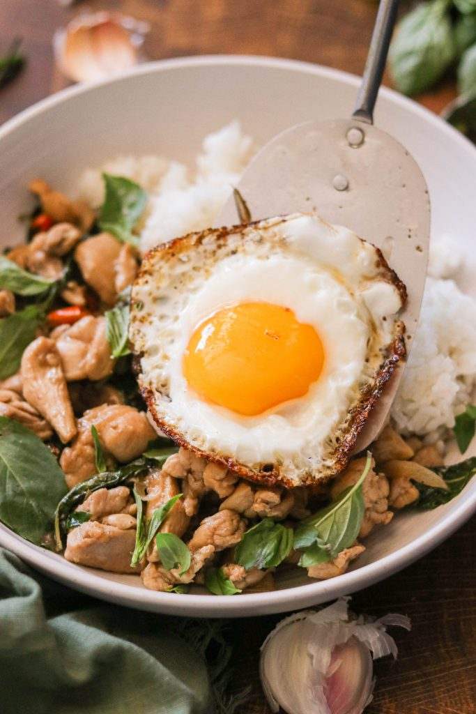 Laying a fried egg over spicy chicken with basil, rice, chilis