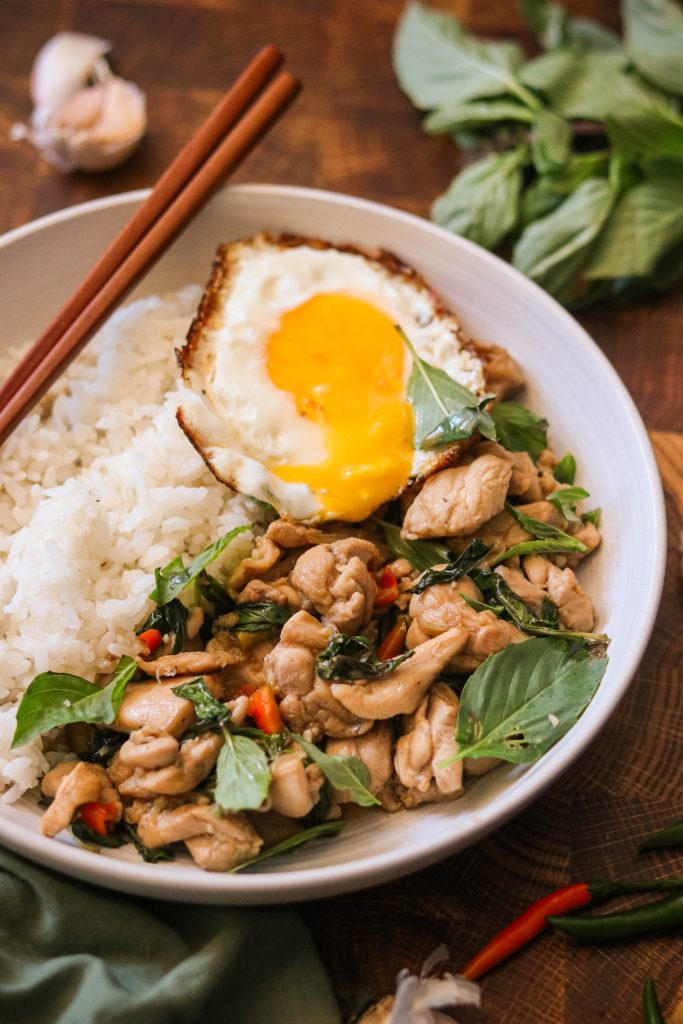Pad Krapow Gai in a bowl with rice and a fried egg