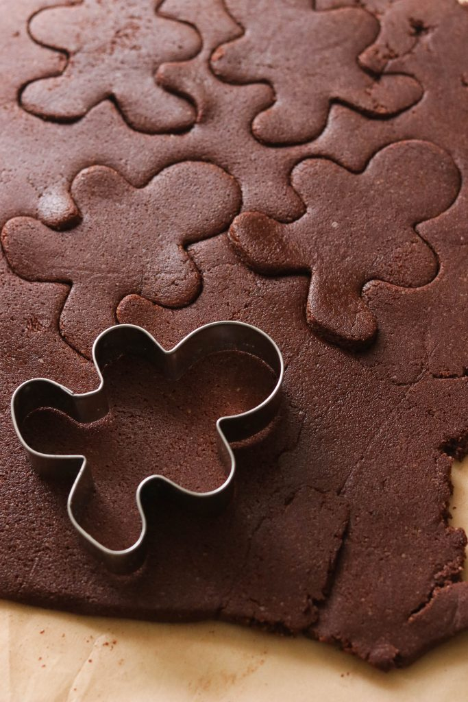 Cutting out gingerbread shapes on gluten free chocolate sugar cookie dough