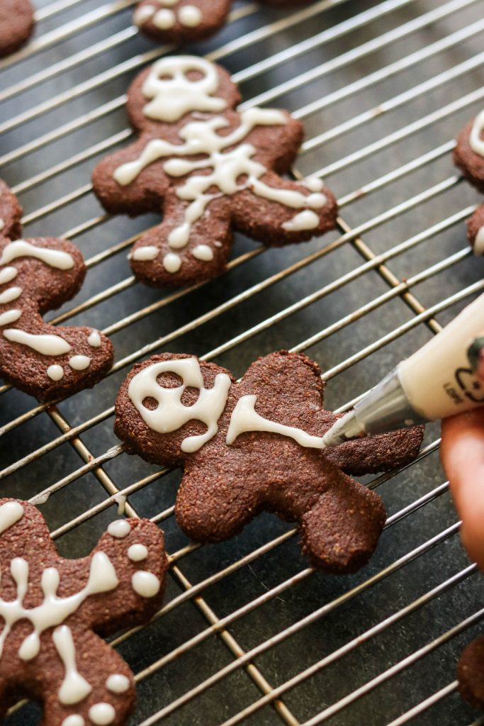 Decorating skeleton gingerbread men with white icing